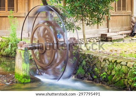Water wheels blurred by long exposure in old town Yantou, Zhejiang province, China - stock photo