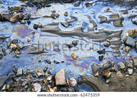 water with different colored patches of gasoline and oil - stock photo