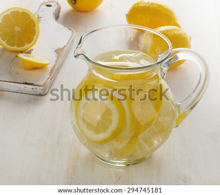 Water with lemon and ice in  glass jug. Selective focus