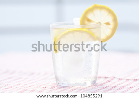 water with lemon and lime in a glass with ice - stock photo