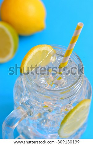 water with lemons and paper straw - stock photo