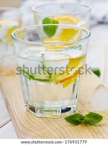 Water with limes, oranges, lemons, ice and mint on a kitchen board - stock photo