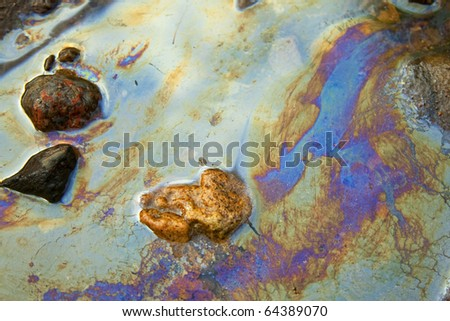 water with patches of gasoline and oil - stock photo