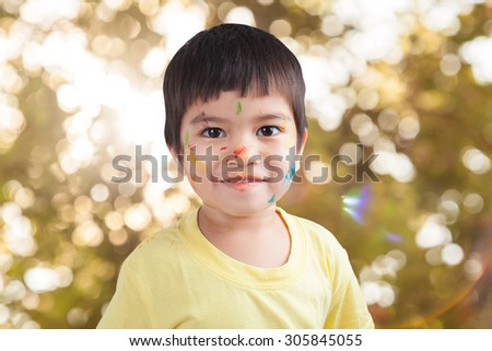 watercolor on face little boy by his play with bokeh background of tree - stock photo