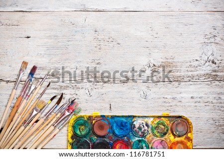 Watercolor paint and brushes on wooden background - stock photo