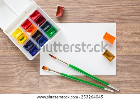 Watercolor paint box, paper and brushes for painting. - stock photo