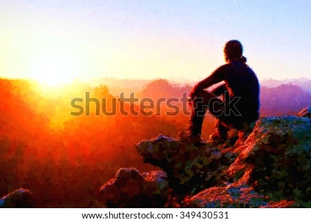 Watercolor paint. Paint effect. Adult tourist in black trousers, jacket and dark cap sit on cliff's edge and looking to misty hilly valley bellow - stock photo