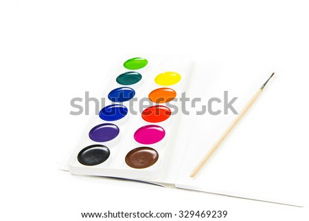 Watercolor paints set and a brush on top of a notebook isolated on a white background - stock photo