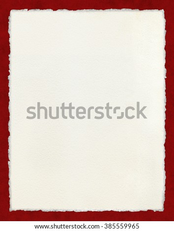 Watercolor paper with true deckled edges on a textured red background.  File includes a clipping path. - stock photo