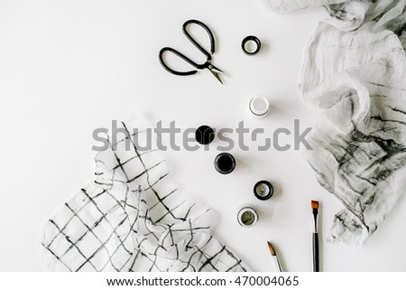 Watercolor, scissors, textile and brushes at white background. Flat lay, top view