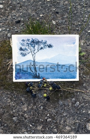 watercolor sketch depicting a tree and mountains in the evening mist. etude photographed on a background of stones, lies next to a branch of blackberry.