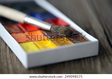 watercolor with brush on wooden table - stock photo