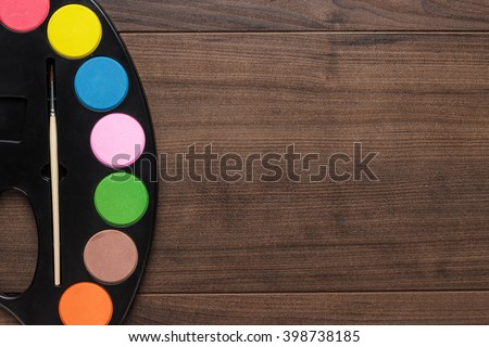 watercolors and brush on the wooden table - stock photo