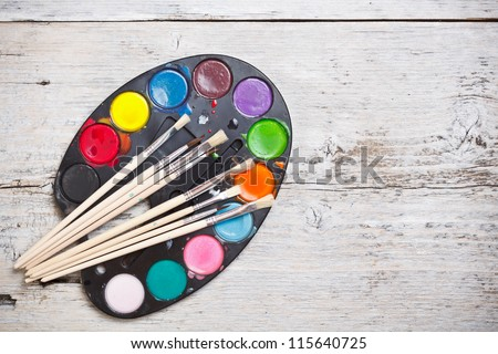 Watercolors and brushes on wood background - stock photo