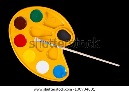 Watercolors and brushes pallete isolated on the black background