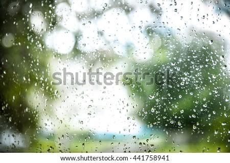 waterdrop on the glass of car on raining day when driving. Fresh rain splash drops on a window - stock photo