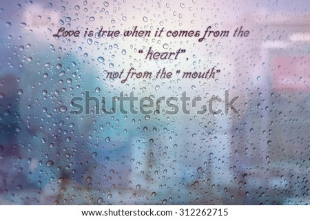 Waterdrops on a glass surface windows with Love from heart qoutes on cityscape background - stock photo