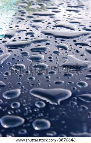 Waterdrops on cars glass roof, close-up photo. Focus on center group of drops. - stock photo