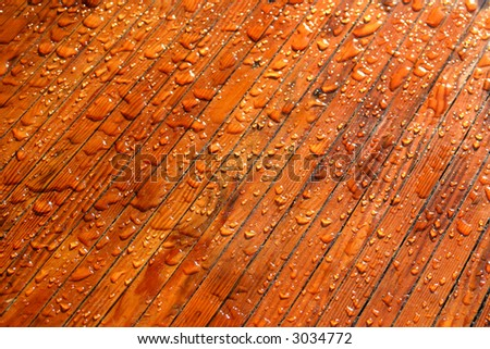 Waterdrops on red brown wood reflecting in the sun. - stock photo