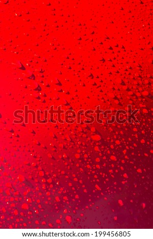 Waterdrops on red metal surface