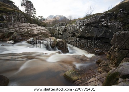 waterfall and fast flowing stream in the scottish highland - stock photo