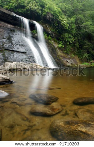 Waterfall and pond in lush green forest - stock photo