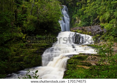 Waterfall and rain forest on the south island of New Zealand - stock photo