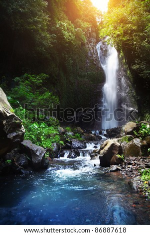 Waterfall and river in deep tropical forest - stock photo