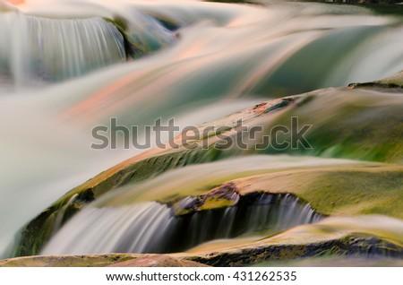 Waterfall and rocks at sunset - stock photo