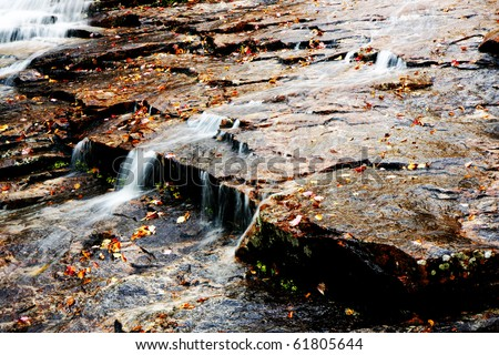 waterfall at fall time with stones and leaves - stock photo