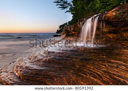 Waterfall at the beach. Taken at Pictured Rocks National Lakeshore, Lake Superior, Michigan, USA - stock photo