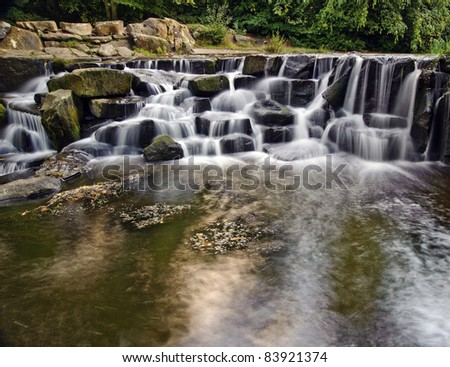 Waterfall cascades flowing over flat rocks in forest landscape - stock photo