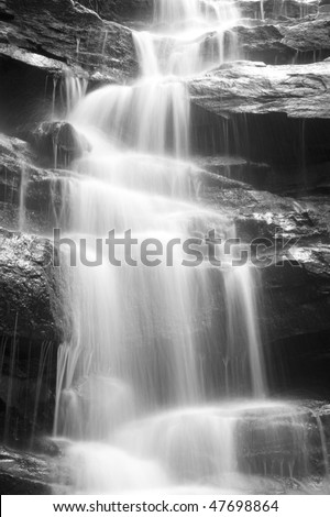 Waterfall cold fresh water stream long shutter speed blurred motion on black stone rocks in park