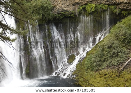Waterfall: Detail of Burney Falls in California's McArthur-Burney Falls Memorial State Park located in Shasta County. Spring water flows out of fissures in the volcanic rock formation. - stock photo