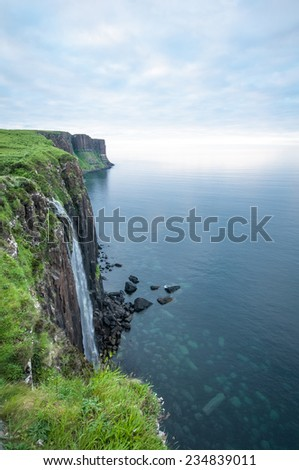 Waterfall falling from high cliffs into the ocean. Isle of Skye, Scotland, UK. - stock photo