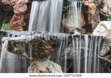 Waterfall flowing motion on stone in the garden.  Beautiful  of waterfalls with soft flowing water and large stone. ( Blur blurred Waterfall)  :Ideal  use for background: - stock photo