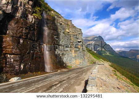 Waterfall flows down from the mountains onto the Going To The Sun Road in Glacier National Park - Montana. - stock photo