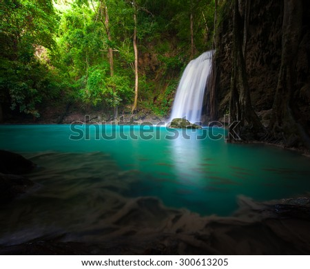 Waterfall flows into lake in forest and sunlight shines through trees and leaves - stock photo