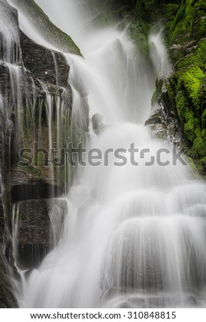 Waterfall flows softly over the rocks - stock photo