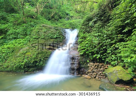 Waterfall in a secret ravine~Cool refreshing waterfall hidden in a mysterious forest of lush greenery - stock photo