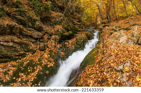 Waterfall in autumn canyon. Natural landscape