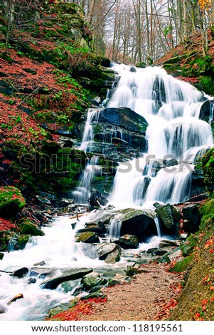 Waterfall in autumn forest - stock photo