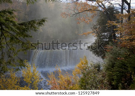 Waterfall in Autumn forest framed by fall foliage