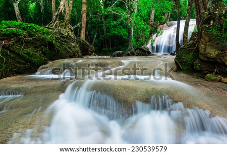 Waterfall in deep tropical forest at Erawan National Park - stock photo
