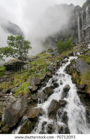 waterfall in foggy mountains landscape