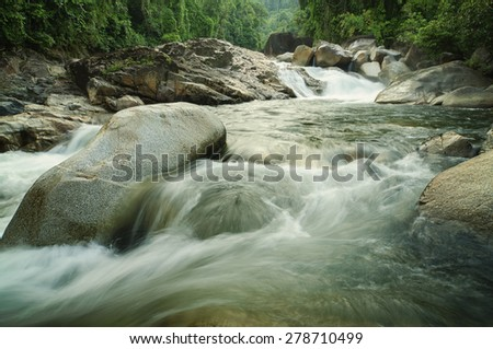Waterfall in forest with foliage and running water texture over boulder rocks   - stock photo
