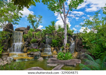 Waterfall in garden at public park with blue sky.