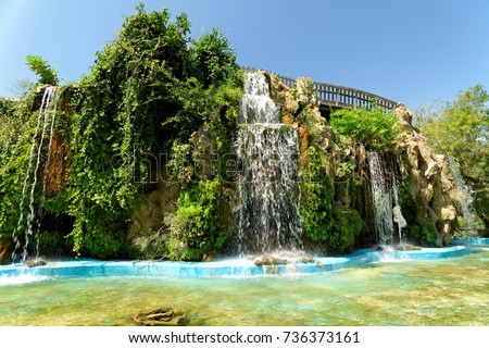 Waterfall in Genoves park, an exotic garden oasis in Cadiz, Spain. It is lined with different species of palm trees, cypresses, and cacti. Many of the plants are brought to Spain from the New World.