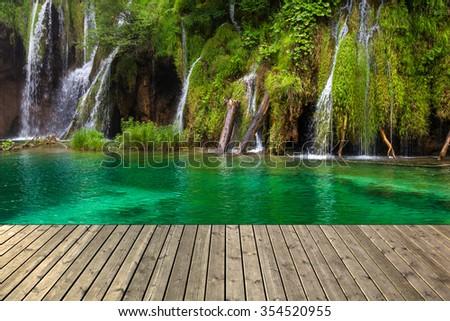 Waterfall in Plitvice lake and wooden plank, Croatia. - stock photo