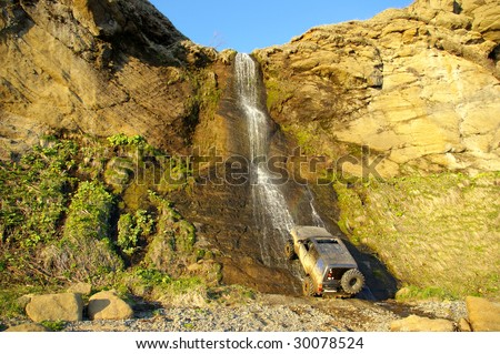 Waterfall in Rocky and car. - stock photo